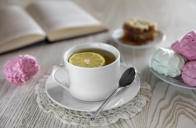 赤スグリのマシュマロと薄緑のリンゴを使った朝食。白い背景とそば蜂蜜のライフスタイルと開いた本のハニカムの背景に白いティーカップとレモンティー。