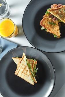 Завтрак с бутербродами на тарелках и ветчиной со столовыми приборами и свежим апельсиновым соком