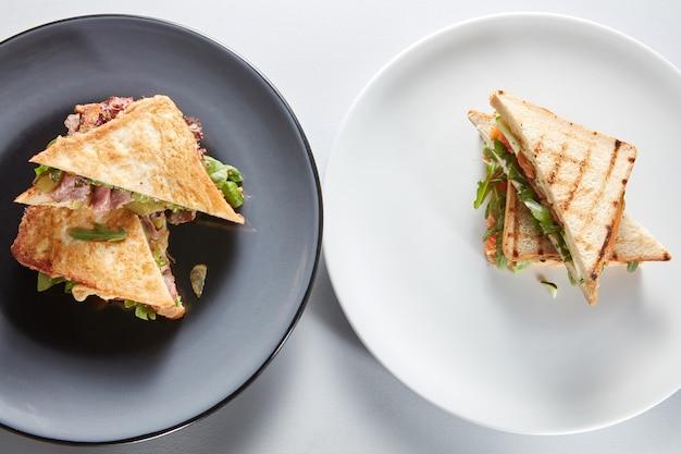 Завтрак с бутербродами на тарелках и ветчиной со столовыми приборами