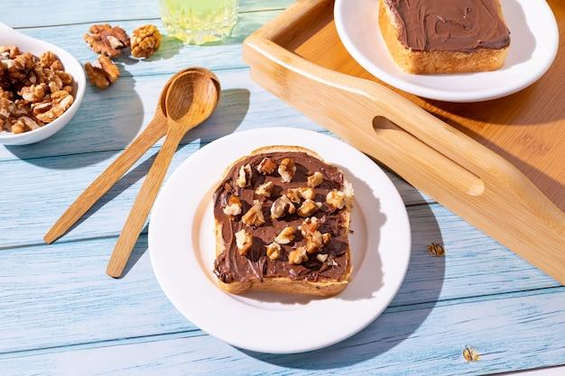 밝은 파란색 배경에 초콜릿 페이스트와 호두를 곁들인 샌드위치로 구성된 아침 식사