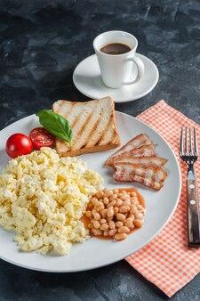 Завтрак с яичницей и беконом на тарелке, черный кофе. фон еда, плоская планировка