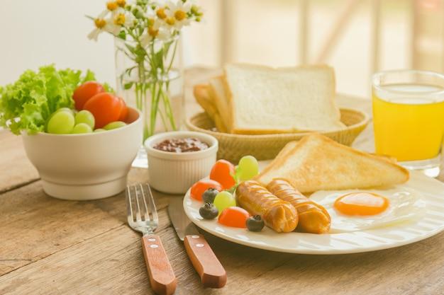 Breakfast with sunny side up fried egg toast sausage fruit vegetable strawberry jam