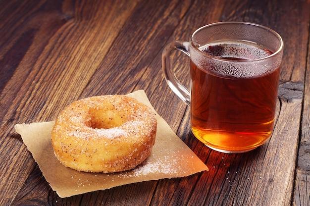 木製のテーブルに甘いドーナツと熱いお茶のカップと朝食