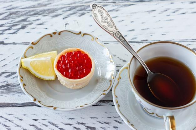 나무 테이블에 빨간 캐비아와 커피를 곁들인 타르트렛으로 아침 식사.
