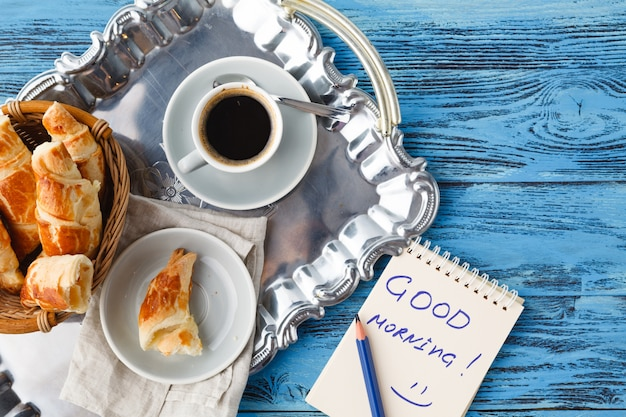 Breakfast with tea and croissant, notes good morning on table
