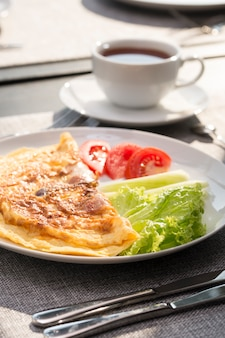 Breakfast with tea and fried eggs with tomatoes and cucumbers and tea