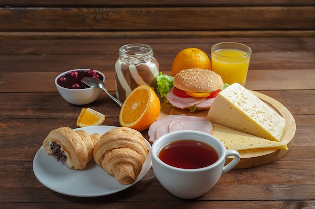 Breakfast with tea, orange juice and croissant on wooden rustic boards