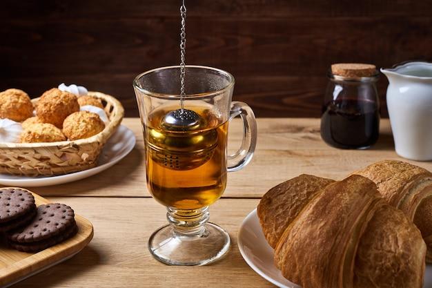 Завтрак с ситечком и конфетами на деревянном столе