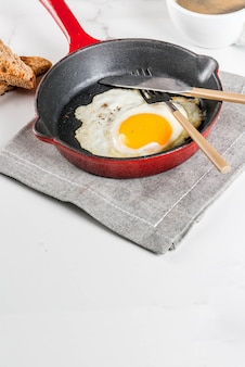 Breakfast with toasted bread, fried egg on iron pan and coffee on white marble scene