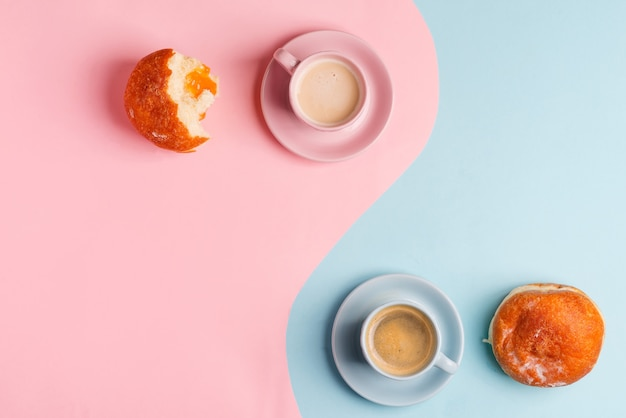 Breakfast with two cups of coffee and homemade freshly baked doughnuts on a duotone pastel pink blue background.