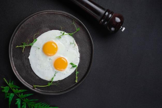 Завтрак с двумя яичницами и зеленью на черном фоне