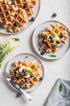 접시에 블루 베리와 시럽을 곁들인 와플과 함께 아침 식사