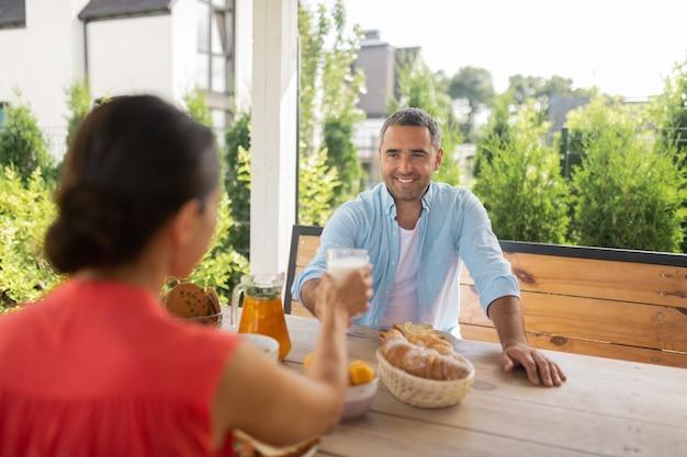 妻との朝食。妻と一緒に外で朝食を食べながら笑っているハンサムなひげを生やした夫