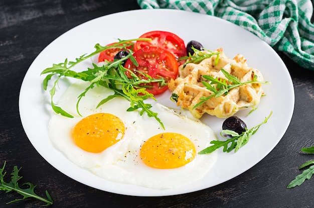 Breakfast with zucchini waffles, fried eggs, tomato, black olives and arugula on white background. appetizers, snack, brunch. healthy vegetarian food.