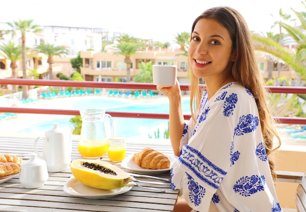 Breakfast woman eating brunch on travel in resort hotel