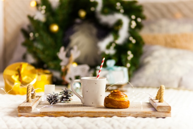 Breakfast on a wooden tray on bed with christmas decoration