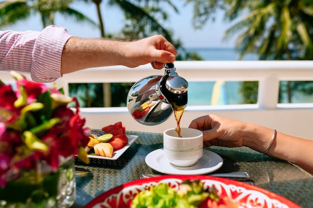 Breakfast a young couple at a tropical resort close-up. a man pours tea to a woman. table is a plate with tropical fruits. summer holidays in hot countries
