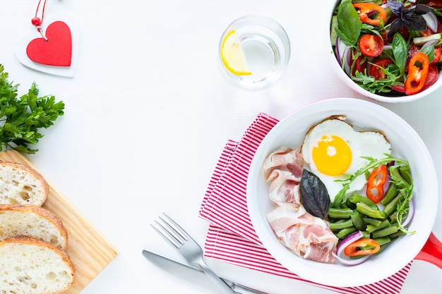 Breakfast for your beloved for the holiday: heart-shaped egg, bacon, green beans on a white table. selective focus. top view. copy space