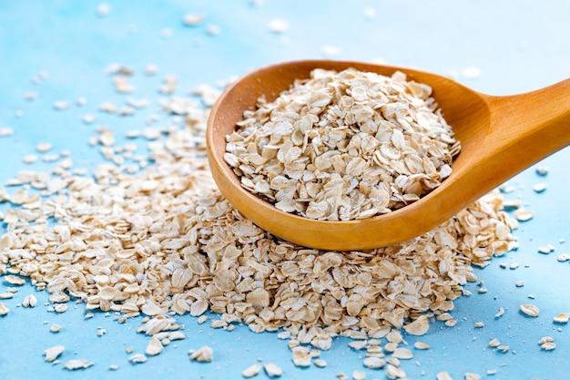 青色の背景に木のスプーンでオートミールを乾燥させます。オーツ麦のフレークで健康的な食事の朝食、breakfast身の食べ物