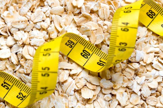 測定テープとオートミールをクローズアップ。健康的な食物繊維の朝食、breakfast身食品