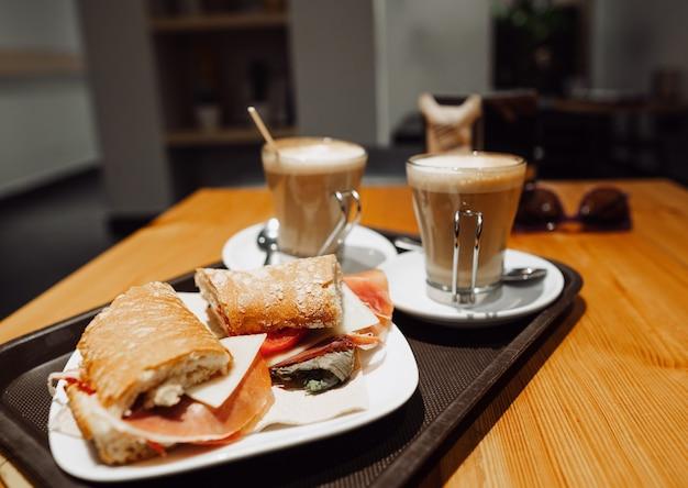 朝食の軽食-ocafeのテーブルにコーヒーラテとボカディージョサンドイッチ