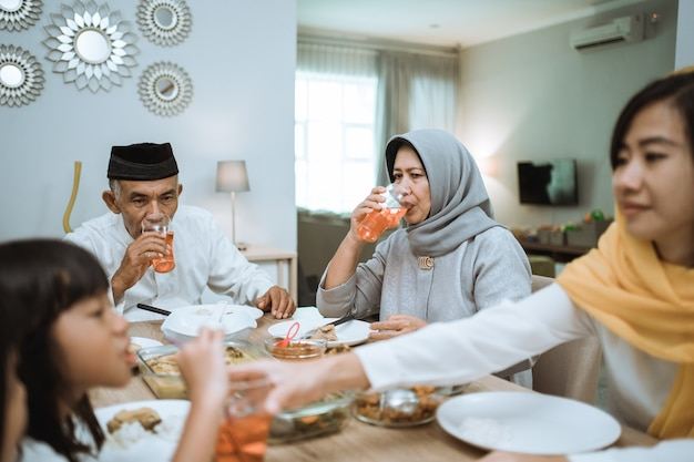 Breaking the fast. muslim asian with hijab having iftar dinner together at home sitting on dining table