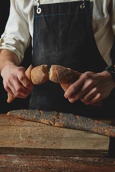 Разрыв свежего хлеба. предпосылка концепции выпечки и приготовления пищи. руки разрывают буханку на деревенском деревянном столе