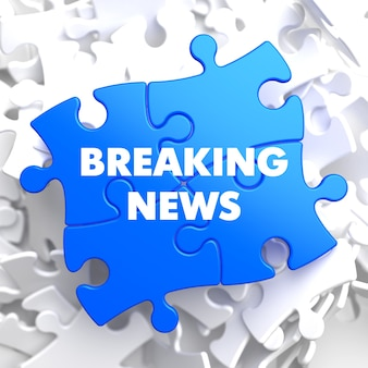 Breaking news on blue puzzle on white background.