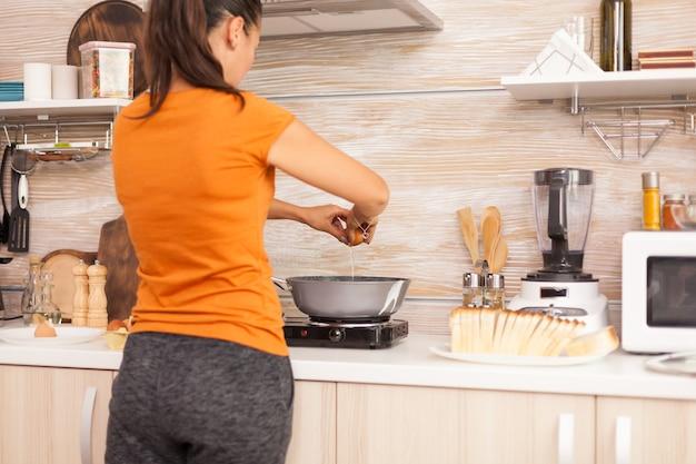 卵を割って、朝食のために鍋でそれらを縁取ります。
