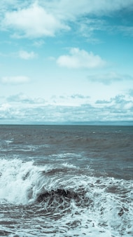 A breaking wave and stormy sea in a vertical panorama format.