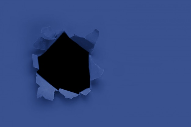 Breakthrough paper hole with black background toned with main trendy classic blue. copyspase