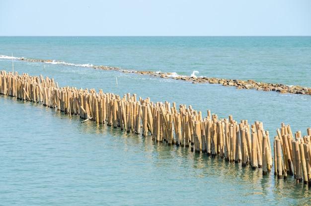 Breakwater. bamboo poles and rock using for break sea wave