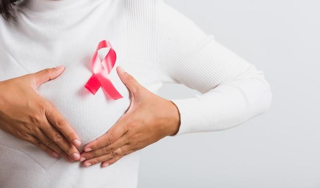 乳がん啓発ヘルスケアアジアの女性は胸にピンクの乳がん啓発リボンを持っています