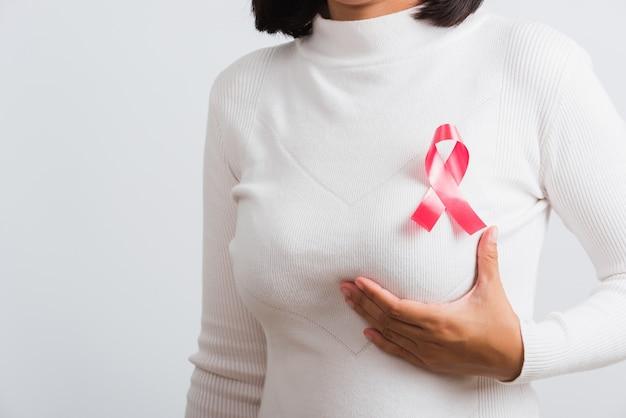 乳がん啓発ヘルスケアアジアの女性彼女は胸に乳がん啓発リボンを持っています