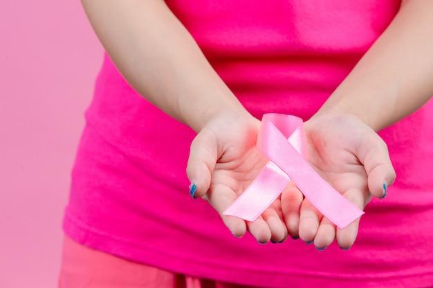 乳がんの意識、両手に女性に置かれたピンクのリボンは、世界乳がんデーのシンボルです。