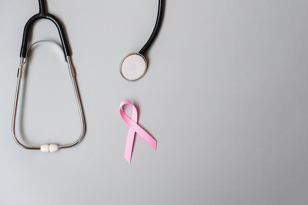 Осведомленность о раке груди, розовая лента со стетоскопом на сером фоне для поддержки людей, живущих и больных. концепция женского здравоохранения и всемирного дня борьбы с раком