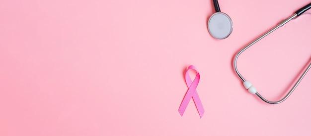 Осведомленность о раке груди, розовая лента со стетоскопом на розовом фоне для поддержки людей, живущих и больных. концепция женского здравоохранения и всемирного дня борьбы с раком