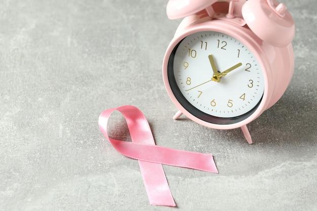 Лента осведомленности рака груди и будильник на сером текстурированном фоне