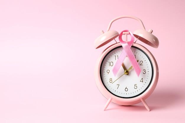 Лента осведомленности рака груди и будильник на розовом фоне