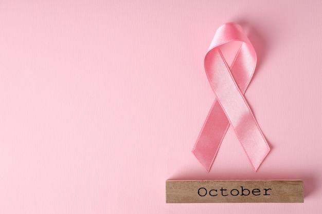 Лента осведомленности рака молочной железы и деревянный блок с текстом октября на розовом фоне
