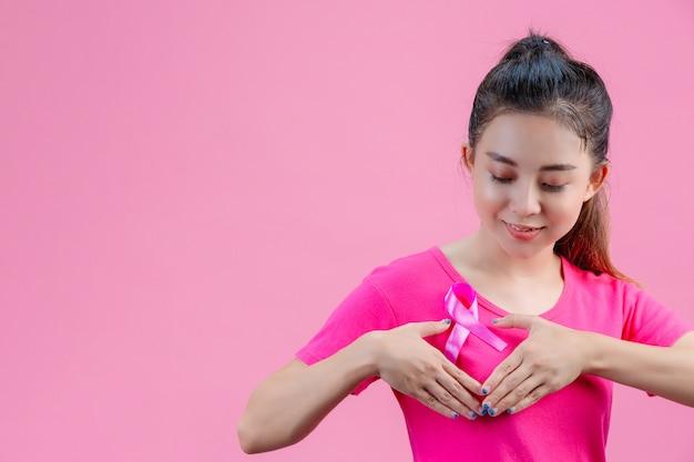 乳がんの意識、胸にサテンのピンクのリボンとピンクのtシャツの女性、シンボル乳がんの意識をサポート