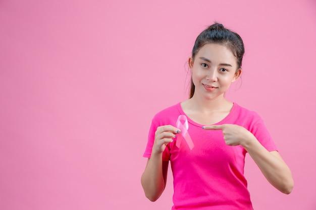 乳がんの意識、ピンクのシャツを着ている女性右手はピンクのリボンを持っています。左手は、乳がんに対する毎日のシンボルを示すリボンを指しています