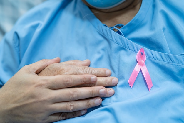 Breast cancer, pink ribbon at asian senior patient for supporting awareness.