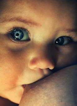 Breast feeding baby with clean blue eyes closeup