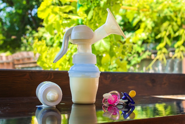 Молокоотсос, бутылка молока и пустышки на столе