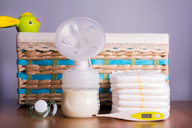 Breast pump, thermometers, diapers and a baby's nipple with wicker basket with a toy