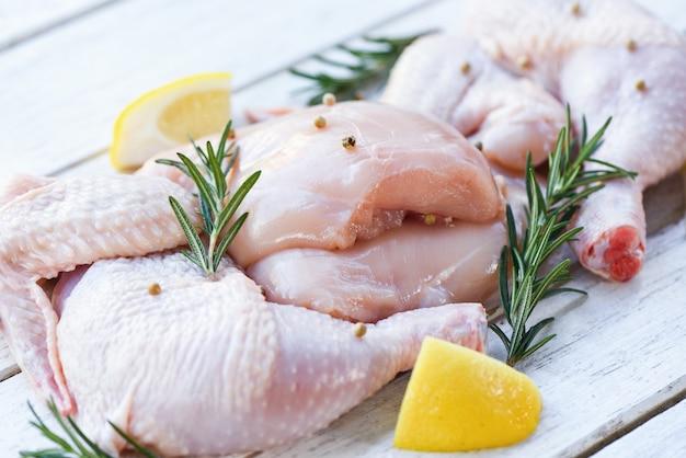 Мясо крыльев и ножки сырого куриного мяса, маринованного с ингредиентами для приготовления пищи - свежая сырая курица с розмарином, лимоном, травами и специями
