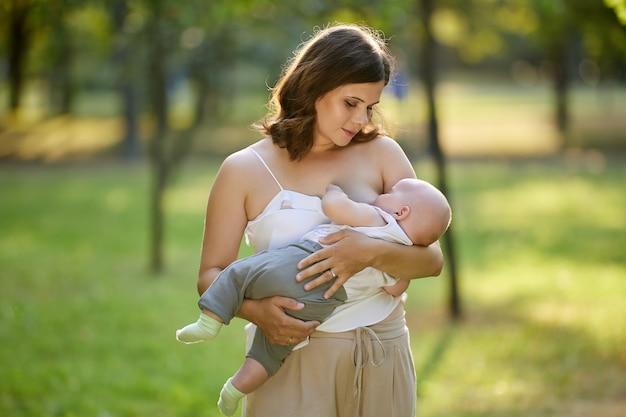 Кормление грудью на публике, мать с маленьким мальчиком в парке