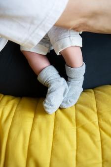 Кормление грудью грудным молоком. маленькие ножки новорожденного в носках. первый месяц жизни малыша.