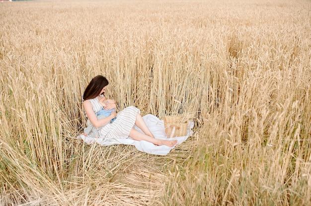 麦畑の暖かい夏の天気のプライバシーで小さな娘に授乳する若い母親の母乳育児